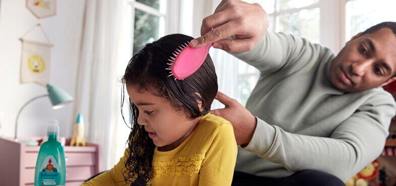 dad brushing daughter hair