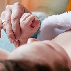 Baby in towel holding mother hand