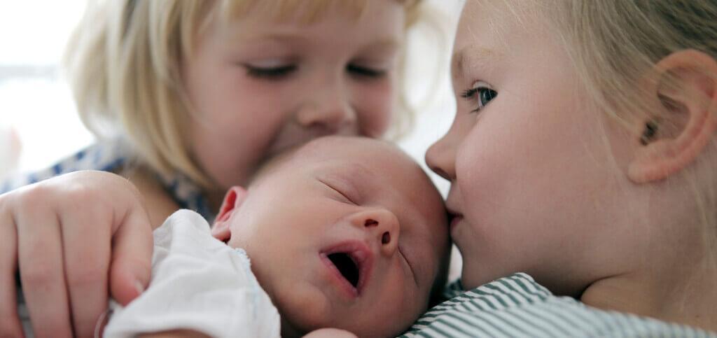 siblings kiss baby